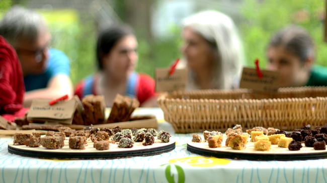 Foto van proefstukjes taart op de voorgrond met op de achtergrond (vlnr) Jos, Anemoon, Marienel en Aster.