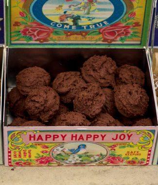 Foto van kleine ronde chocoladekoekjes met cayennepeper in een gekleurd bewaarblikje dat open staat.