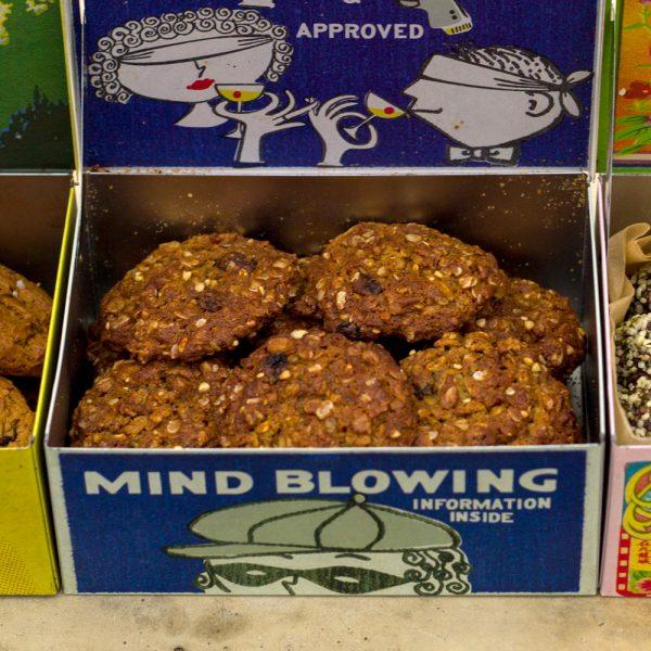 Foto van zachte, traditioneel Amerikaanse oatmeal raisin cookies met kaneel, gember, nootmuskaat en vanille in een gekleurd bewaarblikje dat open staat.