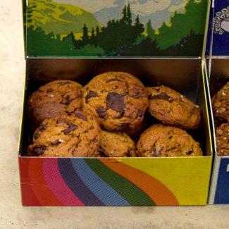 Foto van zachte, traditioneel Amerikaanse chocolate chip cookies met grof zeezout, nootmuskaat en vanille in een gekleurd bewaarblikje dat open staat.