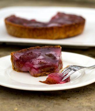 Foto met een stuk pruimentaart gemaakt van ingemaakte pruimen met gebonden pudding en gelei-topping.