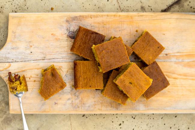 Foto van bovenaanzicht van stukken sinaasappel-cake gevuld met dadels en getopt met sinaasappelgelei op houten plank.