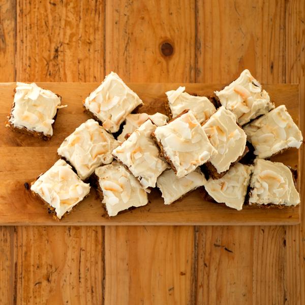 Foto van stukjes worteltaart met citroenfrosting en kokosvlokken.