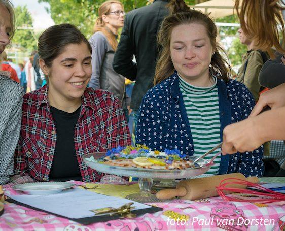 """Foto van (vlnr) Aster en Sara als jury bij """"Heel Utrecht Oost Bakt"""" die taart geserveerd krijgen van de oprichter van Markt om de Hoek, Annejet."""