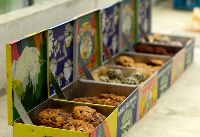 Foto van verschillende soorten koekjes, onder andere chocolate chip en oatmeal, in gekleurde metalen blikjes.