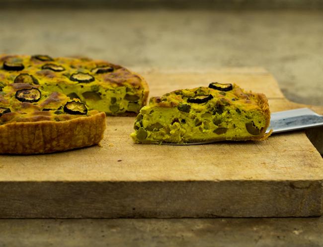 Foto van een stuk vegan quiche met groene groenten op een houten plak.