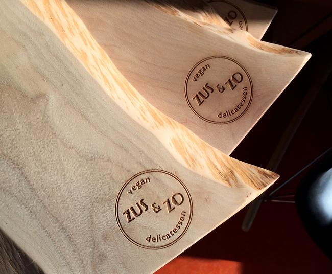 Foto van een ingelaserd Zus&Zo Delicatessen logo op massief houten planken.