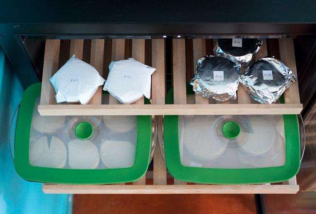 Bovenaanzicht van de bovenste twee planken van de kaaskoelkast, met een aantal ingepakte genummerde kaasjes en een aantal kaasjes in glazen bewaardozen.