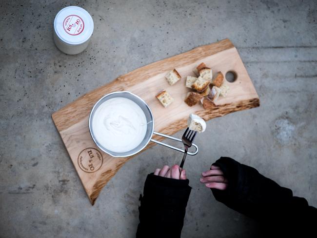 Foto van kaasfondue en brood op Zus&Zo plank en Anemoons handen in een winterjas die een vork met stukje brood gedipt in kaasfondue vasthouden.