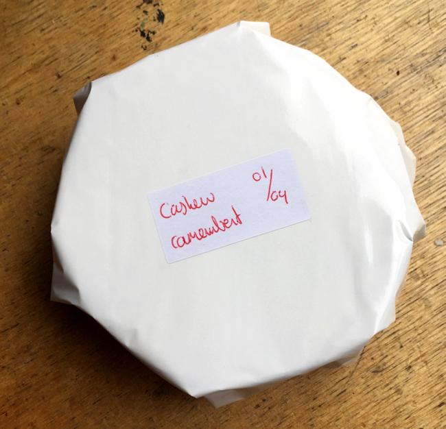 Foto van ingepakte cashewcamembert, met daarop een sticker die aangeeft dat de kaas op 01/04 is ingepakt.