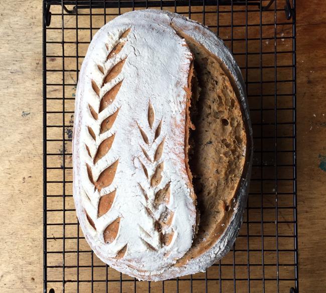 Foto van een zuurdesembrood dat af ligt te koelen op een rooster, met rechts een grote scheur en links twee ingesneden vormen van korenaren.
