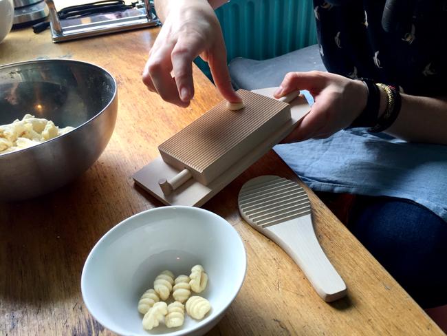 Een afbeelding van een hand die pasta rolt op een gnocchi bord.