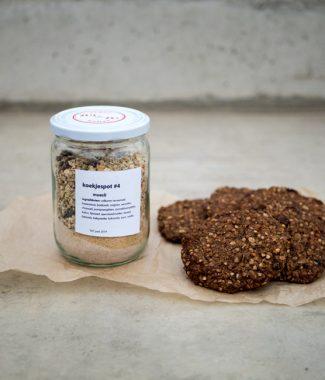 Foto van koekjespot met de ingrediënten voor mueslikoekjes en voorbeelden van de koekjes ernaast.