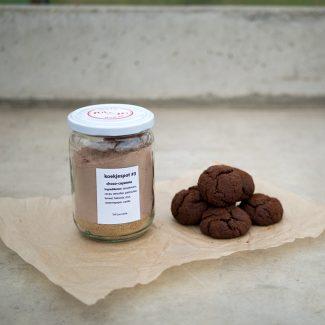 Foto van koekjespot met de ingrediënten voor choco-cayenne koekjes en voorbeelden van de koekjes ernaast.