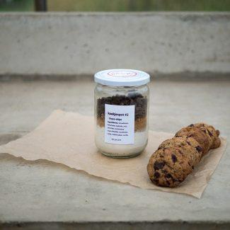 Foto van koekjespot met de ingrediënten voor choco-chip koekjes en voorbeelden van de koekjes ernaast.