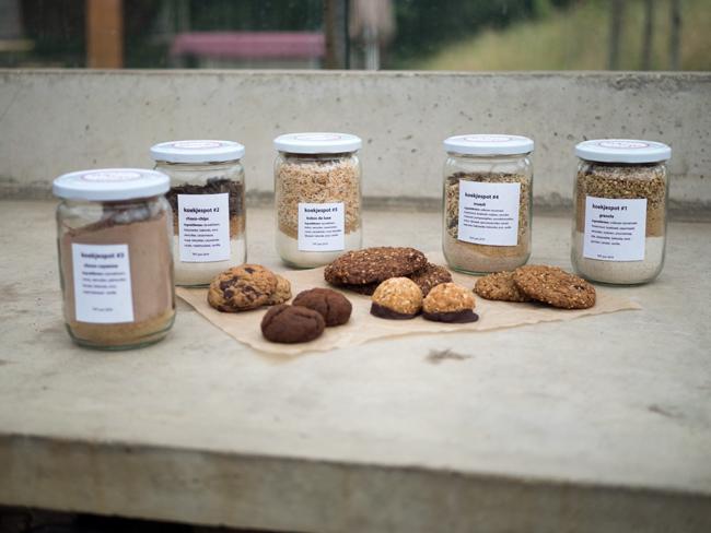 Foto van vijf koekjespotten waarmee met de inhoud koekjes gebakken kunnen worden op een betonnen ondergrond.