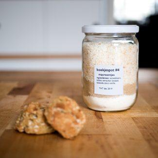 Foto van koekjespot met de ingrediënten voor kokos de luxe koekjes en voorbeelden van de koekjes ernaast.