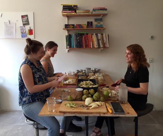 Foto van drie mensen aan een tafel, die 20 kilo peren schillen en klein snijden om in te maken.