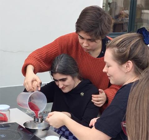 Anemoon, Sara en Aster geven een workshop pruimentaart-bakken op de Universiteit Utrecht voor het Sustasty-Festival van the Green Office Utrecht. Anemoon en Aster schenken samen sap in een cup die Sara vasthoudt.
