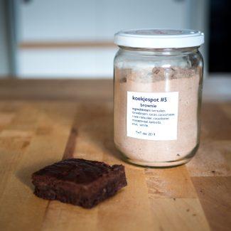 Foto van koekjespot met de ingrediënten voor brownies en voorbeelden van een brownie ernaast.