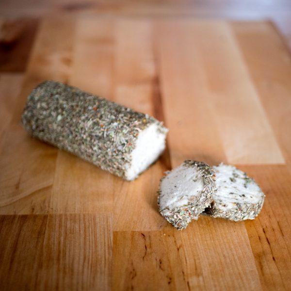 Foto van rolletje cashewkaas in kruiden gerold.