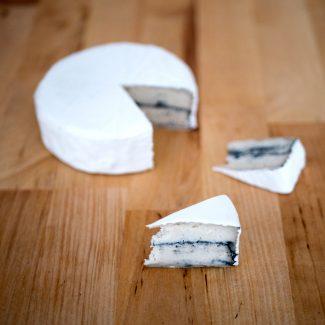 Foto van camembert met as-laag onder de schil.
