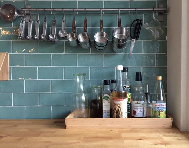 Foto van de maatlepels en -bekers in de Zus&Zo keuken, met daaronder een bakje vol met azijn, agavesiroop, perendiksap, sojasaus en olie.