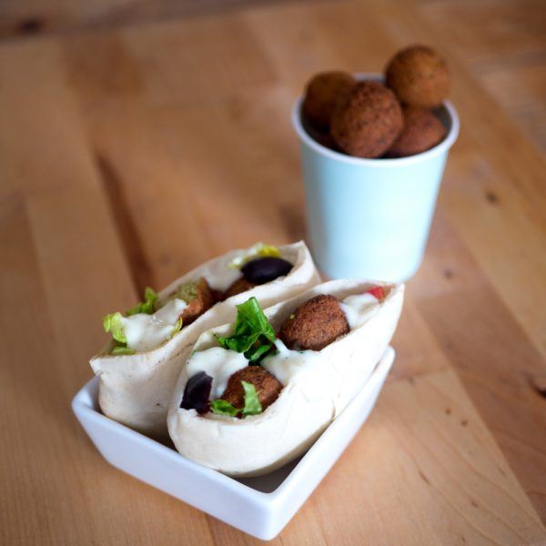 Foto van falafelballetjes in een bekertje en twee halve huisgemaakte pitabroodjes met salade, falafelballetjes en knoflooksaus.
