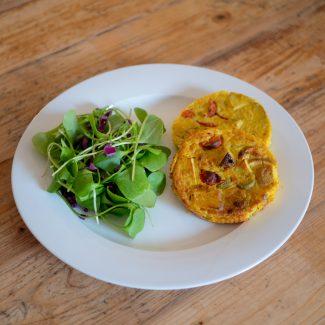 Foto van twee kleine kikkererwtentortilla's met olijf, tomaat en aardappel op een bord met salade.