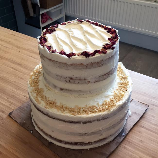 Foto van een bruidstaart met 2 lagen van 3 verdiepingen elk. Het is een naked cake met witte frosting, en rozenblaadjes en hazelnoten als decoratie.