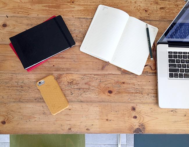 Foto van het werkblad van Zus&Zo met laptop, notitieboekjes, en telefoon in gele pela-case met honingraatpatroon en bijen.