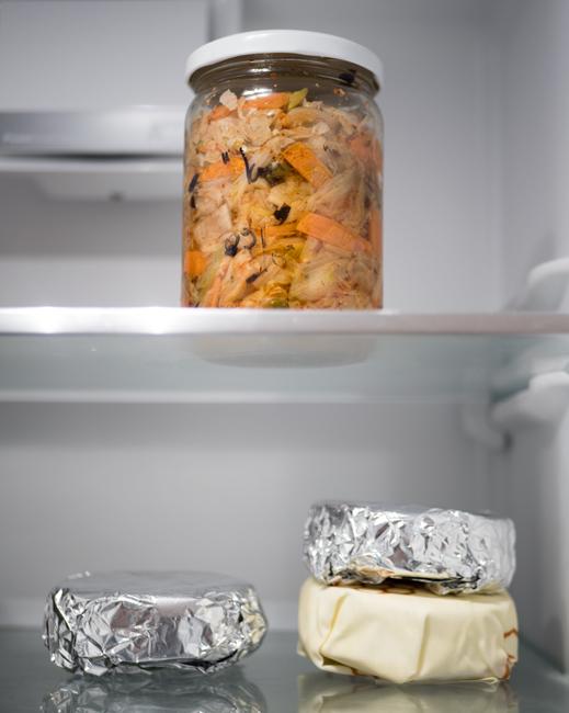 Foto ban Kimchi en 3 ingepakte camemberts in de koelkast.