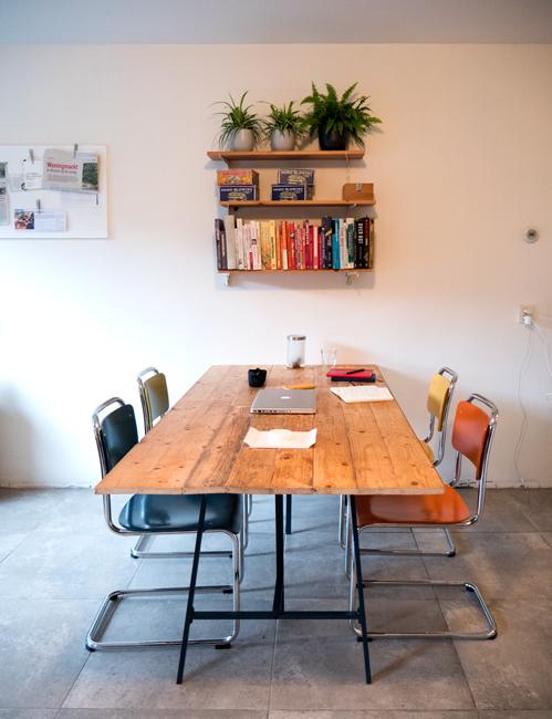 Foto van de keukentafel met vier nieuwe gekleurde tweedehands gispenstoelen.