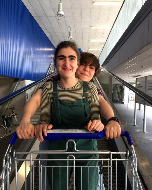 Anemoon en Aster houden samen een winkelwagentje vast terwijl we op de roltrap van ikea naar beneden gaan.