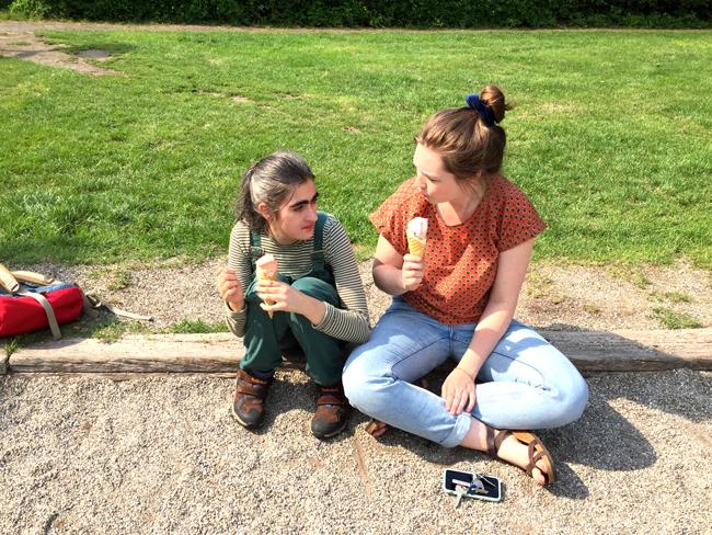 Anemoon en Sara zitten op de rand van een jeu de boule baan op een grasveldje en eten alletwee een ijsje op een (vegan!) hoortje in de zon.