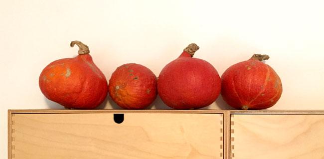 Foto van vier pompoenen op een houten ikea-kastje.
