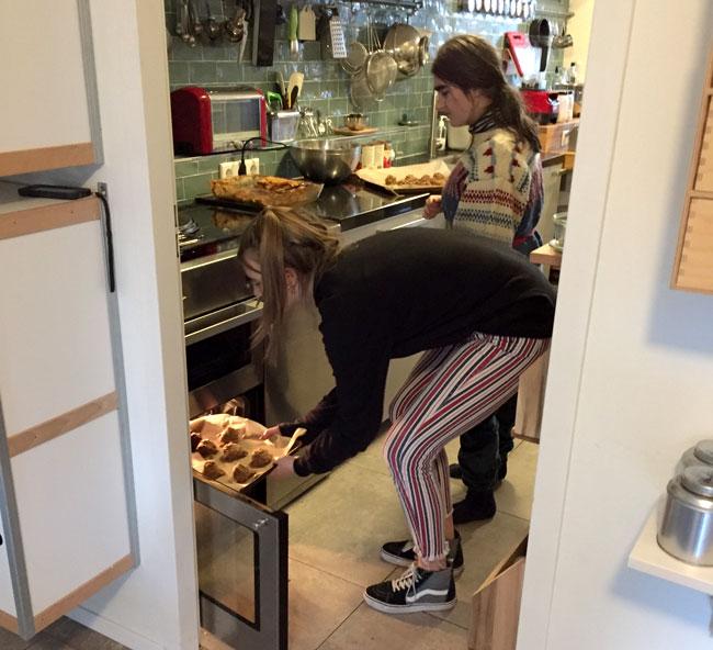 Foto van Jarah en Anemoon die samen een bakplaat met ontbijtkoekjes in de oven doen.