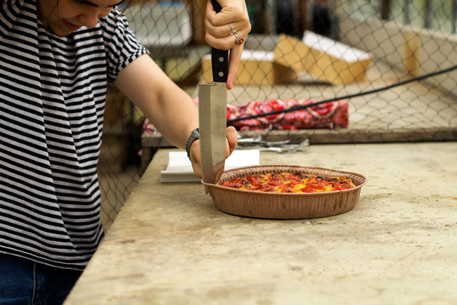 Foto van Aster die met een groot mes quiche uit de papieren bodem snijdt.