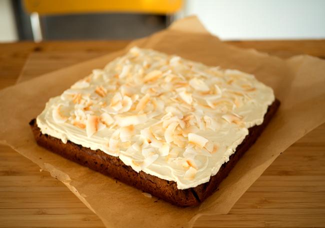Foto van een vierkante worteltaart met citroenfrosting en kokosvlokken.
