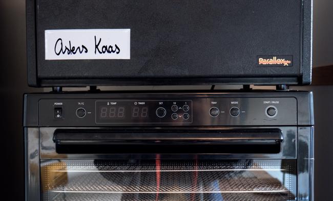 """Detailfoto van een Excalibur dehydrator met daarop de tekst """"Asters Kaas"""" en daaronder het raampje van een Tribest dehydrator."""