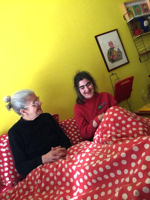 Een foto van Anemoon en Marienel die samen in bed zitten. Anemoon moet hard lachen.